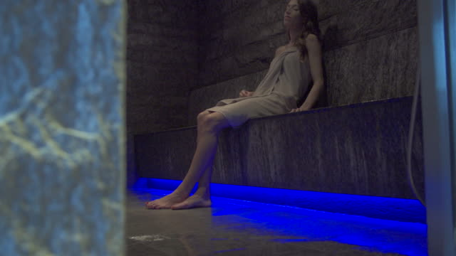 a woman relaxes in a sauna steam bath at a luxury resort. - sauna video stock e b–roll