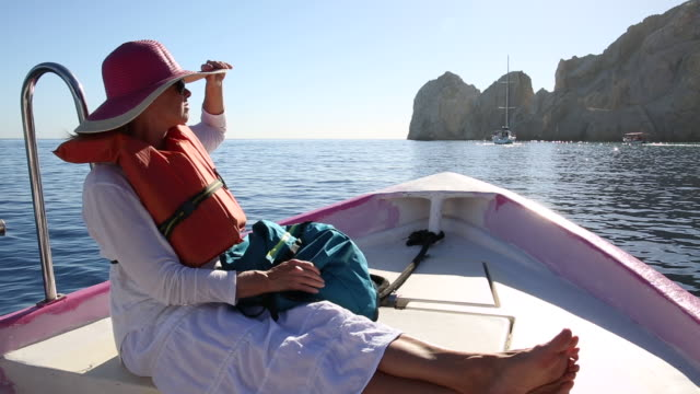 woman relaxes in bow of moving boat, plying tranquil sea - legs crossed at ankle stock videos and b-roll footage