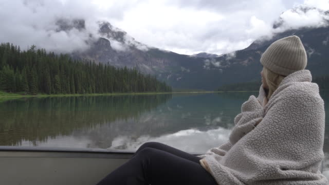 woman relaxes in canoe by lakeshore, wraps herself in blanket to stay warm - eingewickelt stock-videos und b-roll-filmmaterial