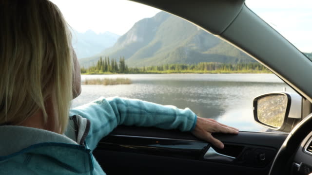 vidéos et rushes de woman relaxes in car, looks out to lake and mountain scene - dimanche