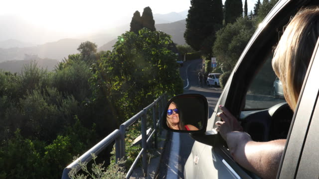 stockvideo's en b-roll-footage met woman relaxes in car, looks out window at sunrise - alleen één oudere vrouw