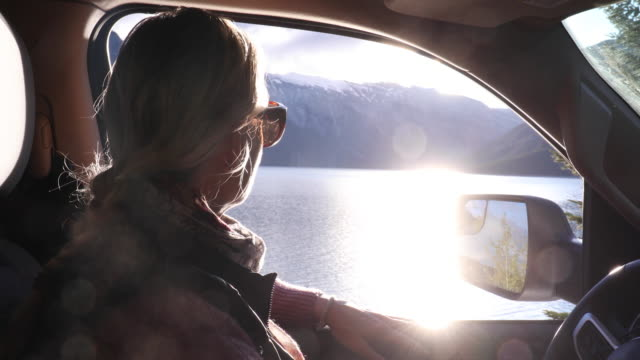 woman relaxes in car seat as window descends - standing water stock videos & royalty-free footage