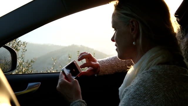 Woman relaxes in car, taking smart phone pic over hills
