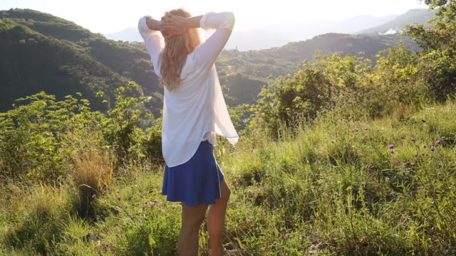Woman relaxes in green meadow, looks out across hills