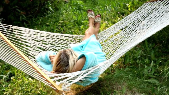 woman relaxes in hammock in meadow, talks on phone - hammock stock videos & royalty-free footage