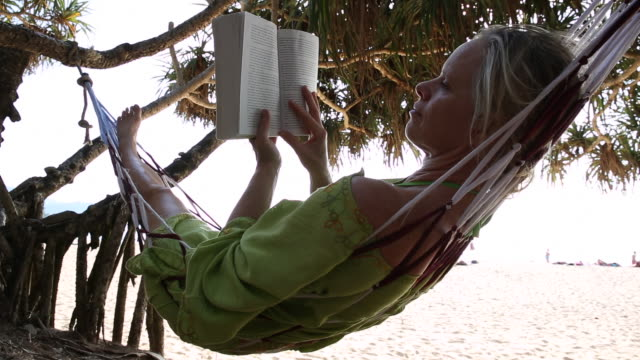 Woman relaxes in hammock, reading book