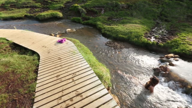 Woman relaxes in hot spring next to boardwalk in Iceland