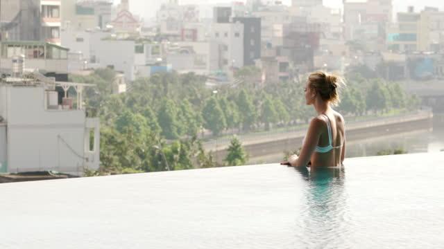 vídeos de stock, filmes e b-roll de mulher relaxa na piscina de beiral infinito com vista cidade - lago infinito