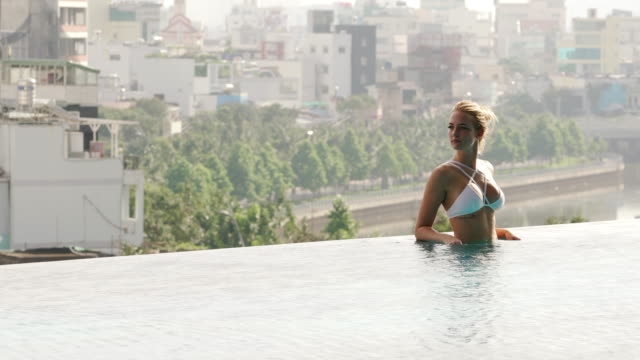 woman relaxes in infinity pool with view of city - infinity pool stock videos & royalty-free footage