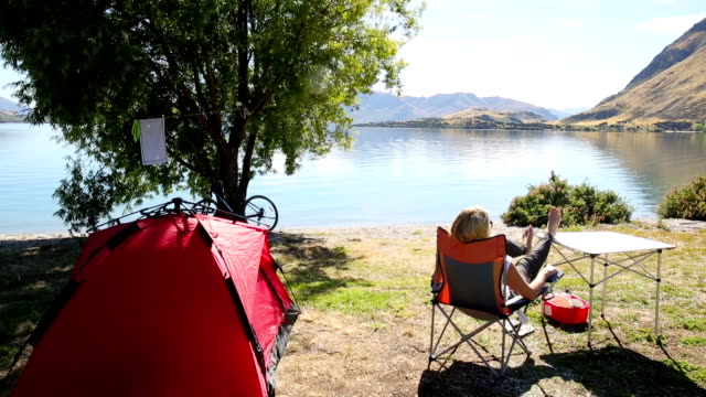 woman relaxes in lakeside campsite, contemplative - legs crossed at ankle stock videos & royalty-free footage