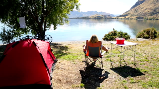 woman relaxes in lakeside campsite, contemplative - 座る点の映像素材/bロール