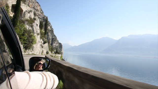 Woman relaxes in passenger seat of moving car, lake below