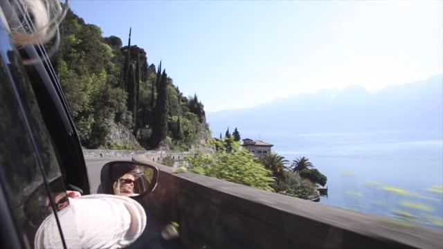 Femme se détend dans le siège passager de la voiture en mouvement, lac ci-dessous