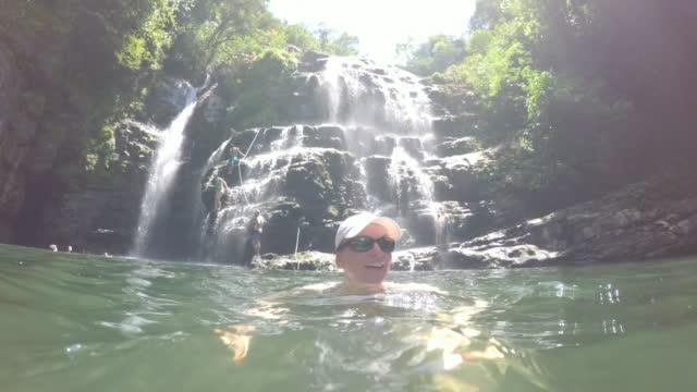 Frau entspannt im Pool unter tropischen Wasserfall