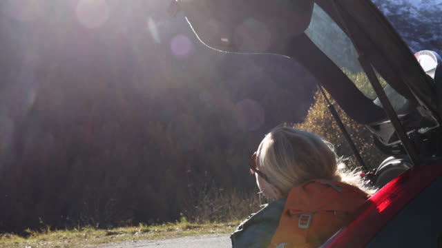 stockvideo's en b-roll-footage met woman relaxes in rear hatch of car, after hiking - hatch