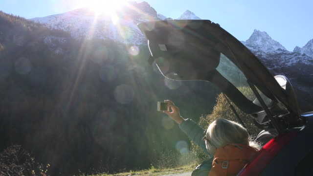 stockvideo's en b-roll-footage met woman relaxes in rear hatch of car, companion joins her - hatch