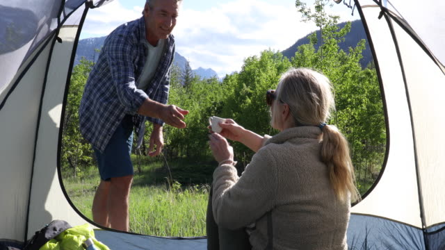 stockvideo's en b-roll-footage met woman relaxes in tent, looks off to mountains and green forest glade - mouw