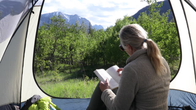 woman relaxes in tent, looks off to mountains and green forest glade - individuality stock videos & royalty-free footage