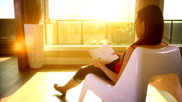 Woman relaxes in the evening sun reading a book