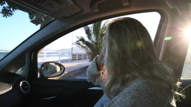 Woman relaxes in vehicle while watching surf behind