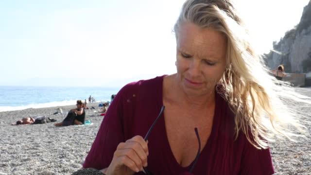 vidéos et rushes de femme se détend sur la plage, nettoie les verres et ressemble au large - port