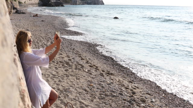 woman relaxes on beach, using digital tablet - tunic stock videos & royalty-free footage