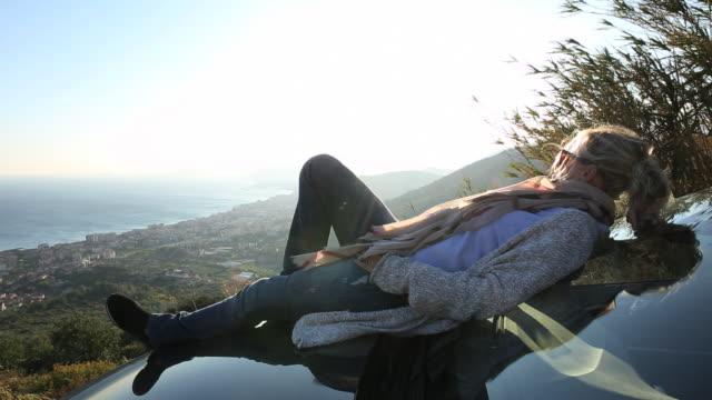 Woman relaxes on car hood, looks off towards sea