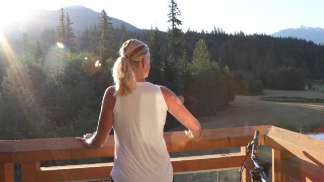 vídeos y material grabado en eventos de stock de woman relaxes on deck at sunrise, look out to mountain scene - manillar