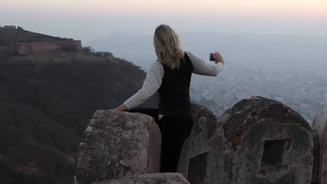 kvinna slappnar på fästning vägg vid soluppgången - endast en medelålders kvinna bildbanksvideor och videomaterial från bakom kulisserna