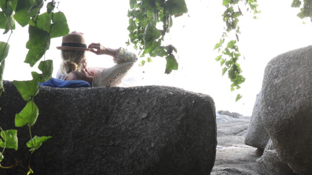 woman relaxes on granite boulder, wearing hat - one mature woman only stock videos & royalty-free footage