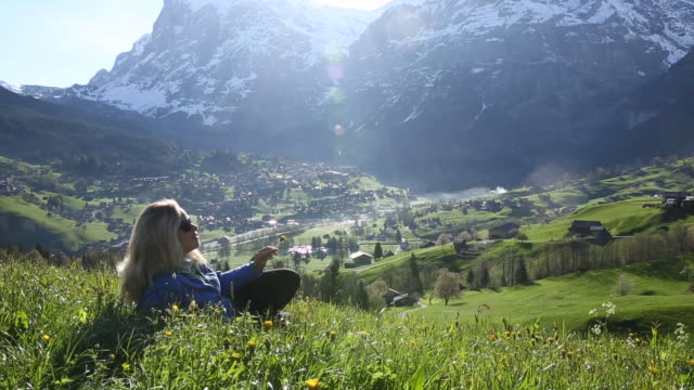 woman relaxes on grassy mountain meadow crest, sunrise - dorf stock-videos und b-roll-filmmaterial