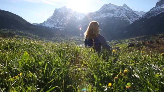 Woman relaxes on grassy mountain meadow crest, sunrise