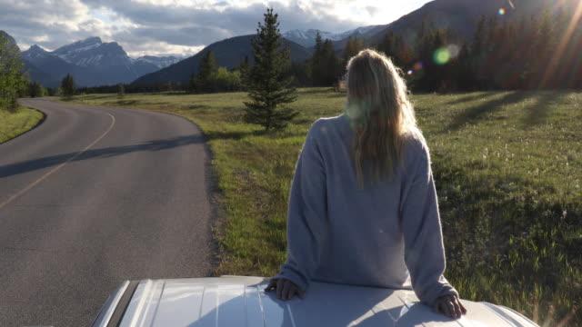 vidéos et rushes de woman relaxes on hood of vehicle, mountain road at sunrise - quinquagénaire