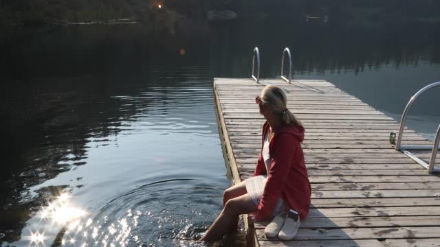 frau entspannt am see pier bei sonnenaufgang, in bergen - dreiviertelansicht stock-videos und b-roll-filmmaterial