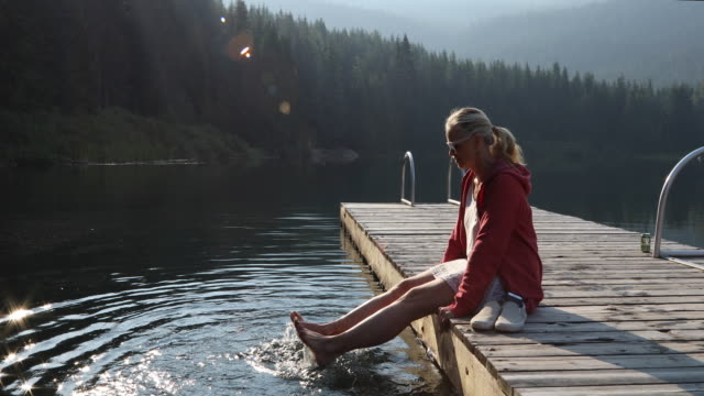 kvinna slappnar på sjön piren vid soluppgången, i bergen - endast en medelålders kvinna bildbanksvideor och videomaterial från bakom kulisserna