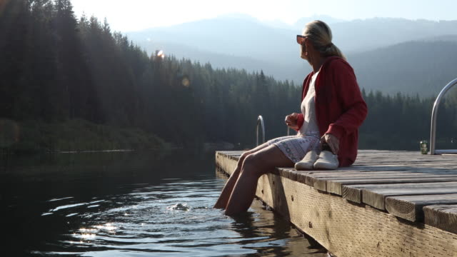 Woman relaxes on lake pier at sunrise, in mountains