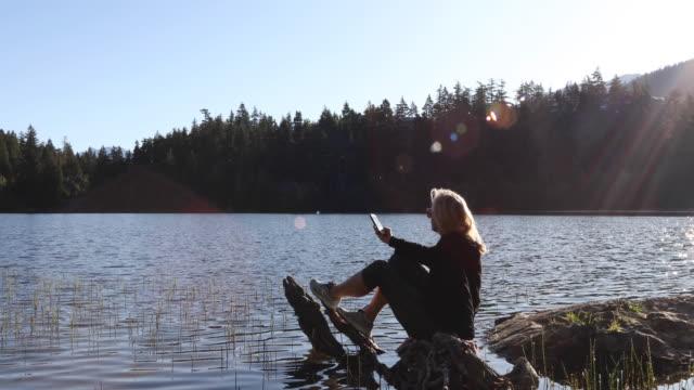 vídeos de stock e filmes b-roll de woman relaxes on log at mountain lake, sunrise - video call