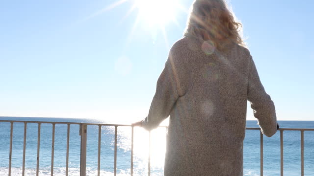 woman relaxes on railing above sea at sunrise - only mature women stock videos & royalty-free footage