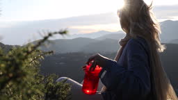 Woman relaxes on rock ledge after ascent, drinks from water bottle