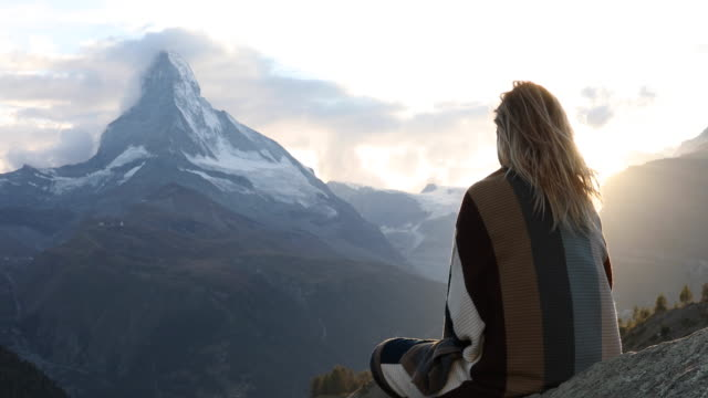 woman relaxes on rock ledge, cloaked in blanket - schweiz stock-videos und b-roll-filmmaterial