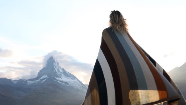 woman relaxes on rock ledge, cloaked in blanket - blanket stock videos & royalty-free footage