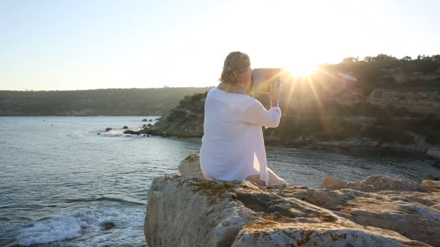 Woman relaxes on rock promontory, taking pic with digital tablet