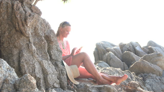 woman relaxes on rock stairs, sending text on phone - pct stock videos and b-roll footage