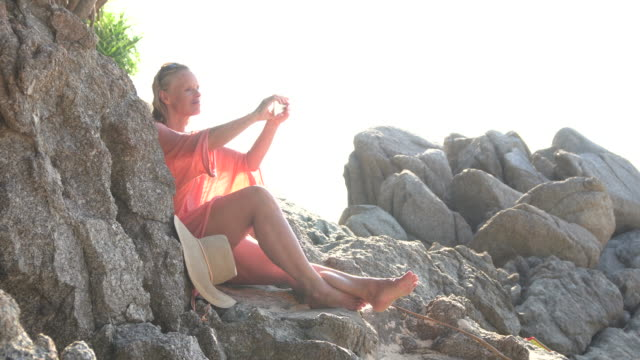 woman relaxes on rock stairs, takes pic with phone - pct stock videos and b-roll footage