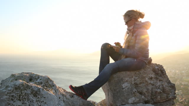 Woman relaxes on rocks, using digital tablet, above sea