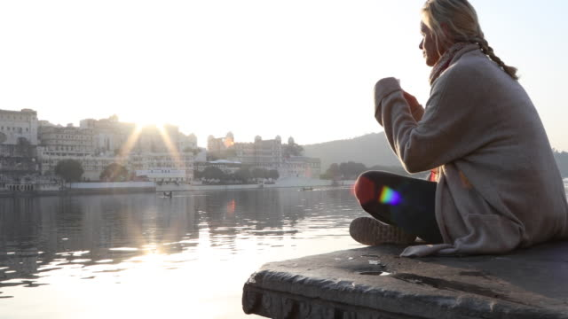 vídeos de stock e filmes b-roll de woman relaxes on stone ghat above lake, looks off - cachecol