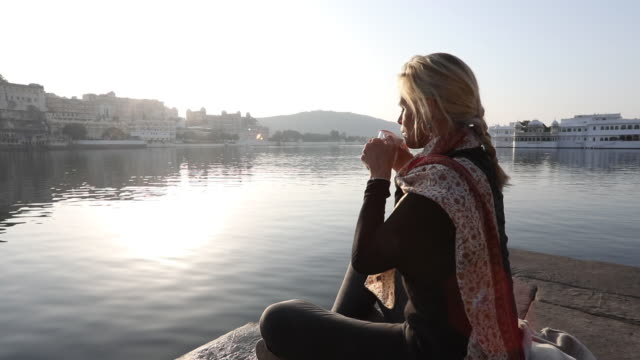 woman relaxes on stone ghat above lake, looks off - mature women stock videos & royalty-free footage