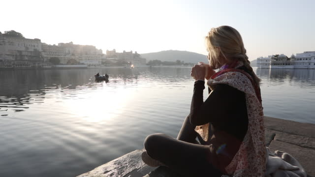 woman relaxes on stone ghat above lake, looks off - locs hairstyle stock videos & royalty-free footage