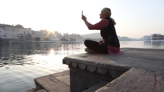 Woman relaxes on stone ghat above lake, takes smart phone pic