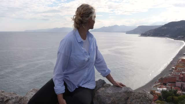 woman relaxes on stone wall above sea, coastline - stone wall stock videos and b-roll footage
